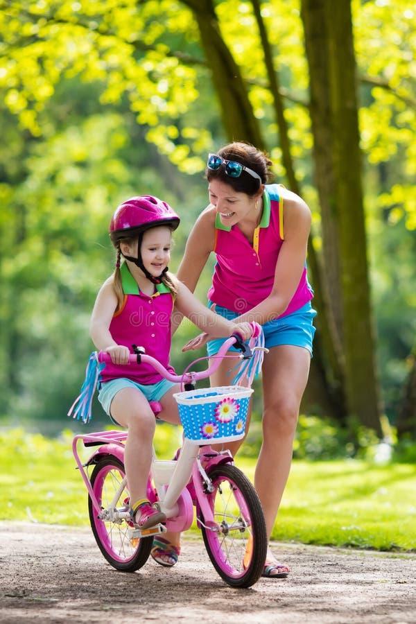 Enfant de enseignement de mère pour monter un vélo image stock