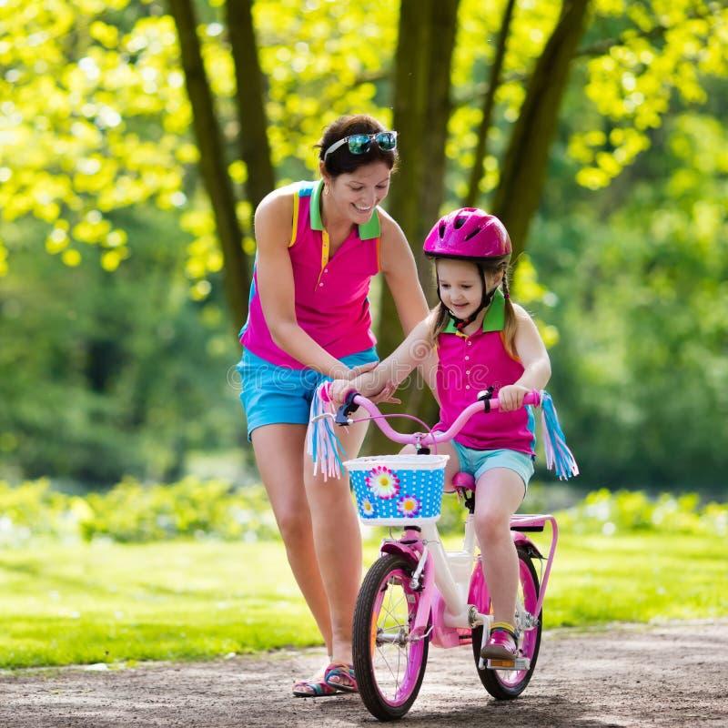 Enfant de enseignement de mère pour monter un vélo image libre de droits