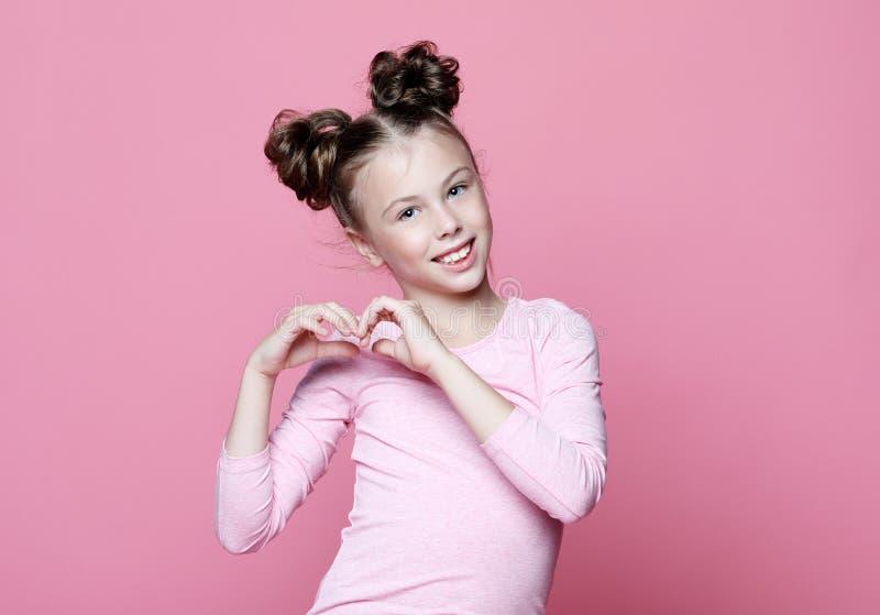 Enfant de fille au-dessus de fond rose souriant dans l'amour montrant le symbole et la forme de coeur avec des mains image stock