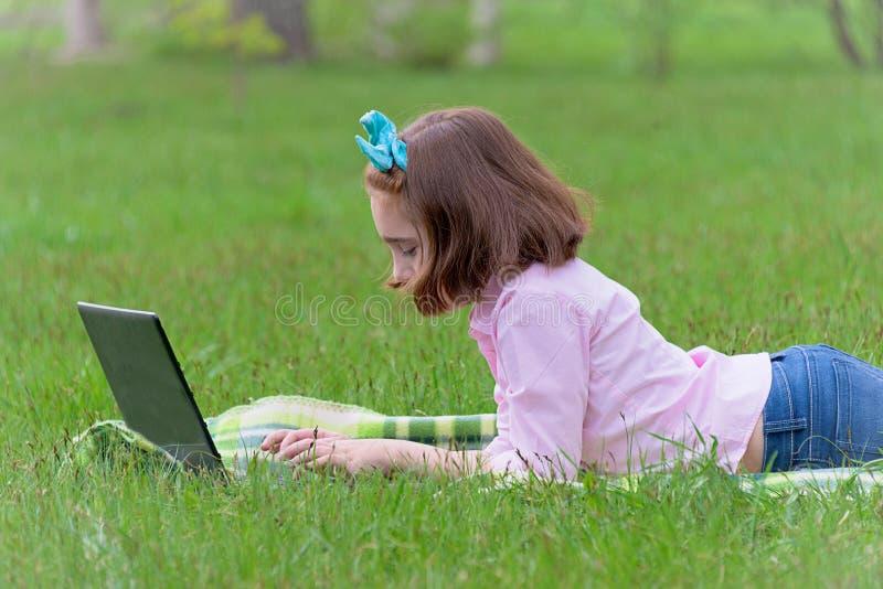 Enfant de fille avec l'ordinateur portable dehors photos stock