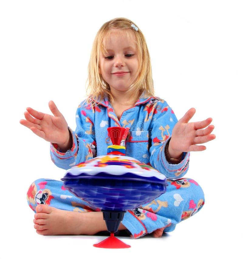Enfant de fille avec le dessus de rotation photo stock