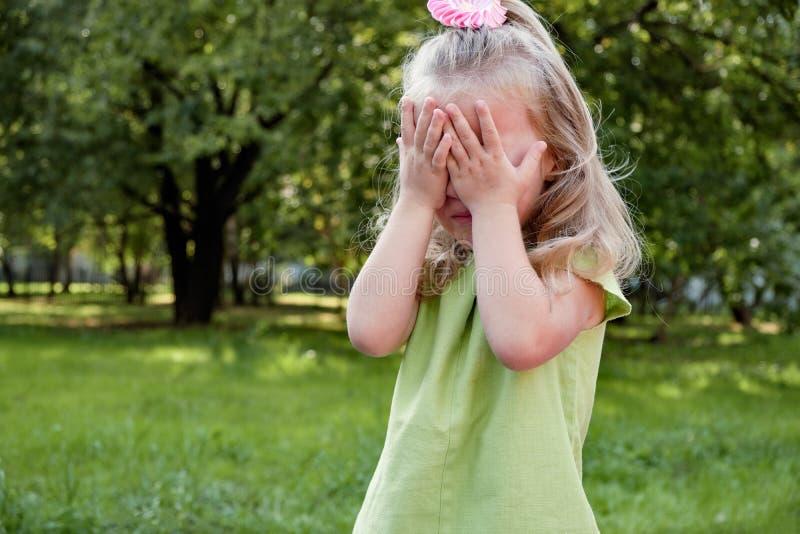 Enfant de fille de renversement pleurant en parc Parenting, psychologie de l'enfant photos stock