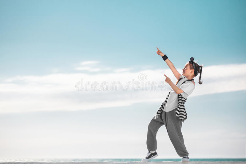 Enfant de fille se dirigeant sur l'espace de copie au-dessus du fond de ciel Gosse de mode photo libre de droits