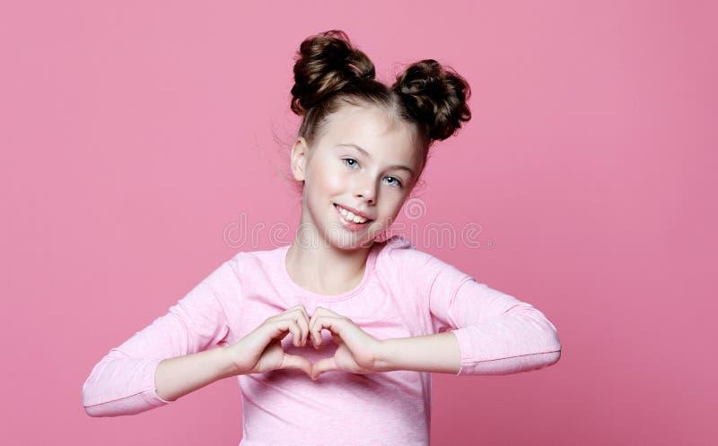 Enfant de fille souriant dans l'amour montrant le symbole et la forme de coeur avec des mains photographie stock