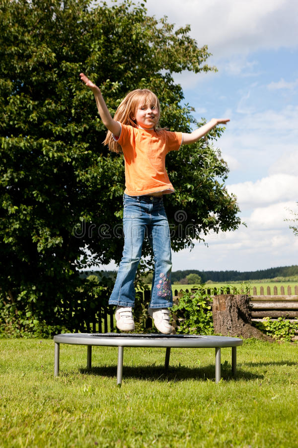 Enfant de fille sur le tremplin dans le jardin photographie stock libre de droits