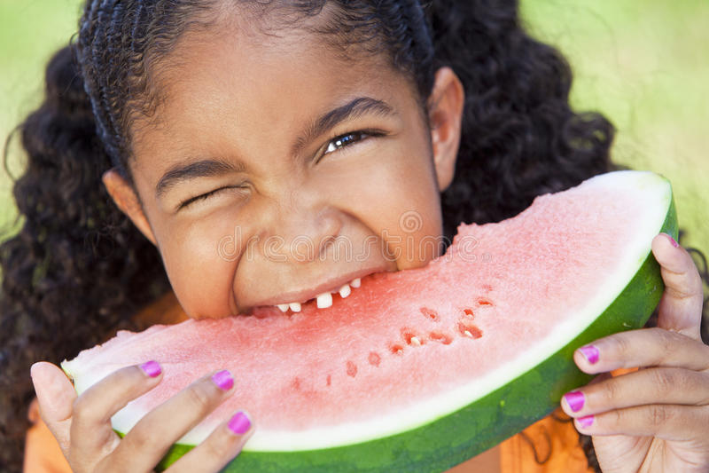 Enfant de filles d'Afro-américain mangeant le melon d'eau photos libres de droits