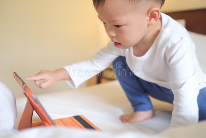 enfant de garçon d'enfant en bas âge s'asseyant dans le lit jouant avec le PC de comprimé photo stock