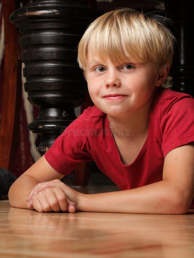 Enfant de garçon s'asseyant sur l'étage photo stock