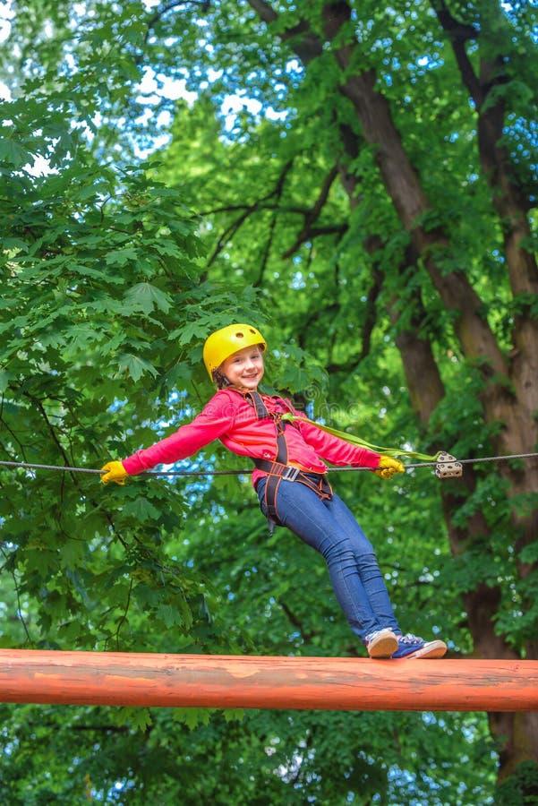 Enfant de grimpeur sur la formation Enfant s'?levant sur le haut parc de corde Rondin s'?levant de filet pour fret et accrochant  photo libre de droits