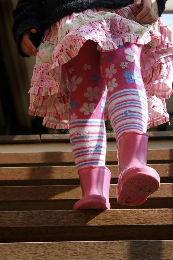 Enfant de jeune fille descendant des escaliers dans les bottes de caoutchouc roses et l'habillement lumineux d'hiver tenant des j image stock