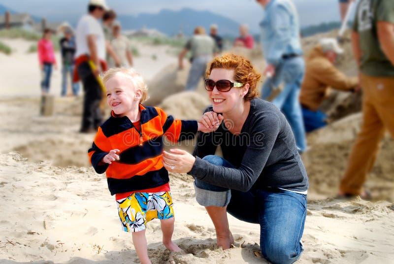 Enfant de mère sur la plage avec des châteaux de sable de bâtiment de foule photographie stock libre de droits
