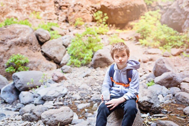 Enfant de petit garçon buvant l'eau minérale mis en bouteille sur la traînée de montagne photo stock