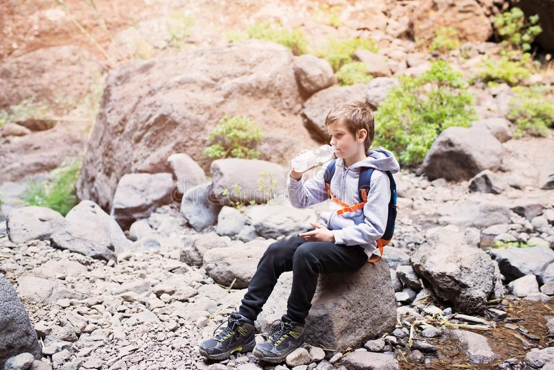 Enfant de petit garçon buvant l'eau minérale mis en bouteille sur la traînée de montagne photo libre de droits