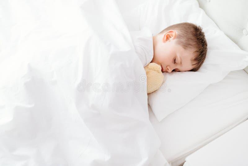 Enfant de petit garçon dormant dans le lit image libre de droits