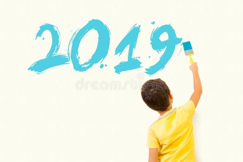 Enfant de petit garçon de Te écrivant la nouvelle année 2019 avec la brosse de peinture photos stock