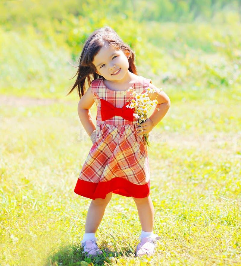 Enfant de petite fille avec des fleurs dehors en été photos stock
