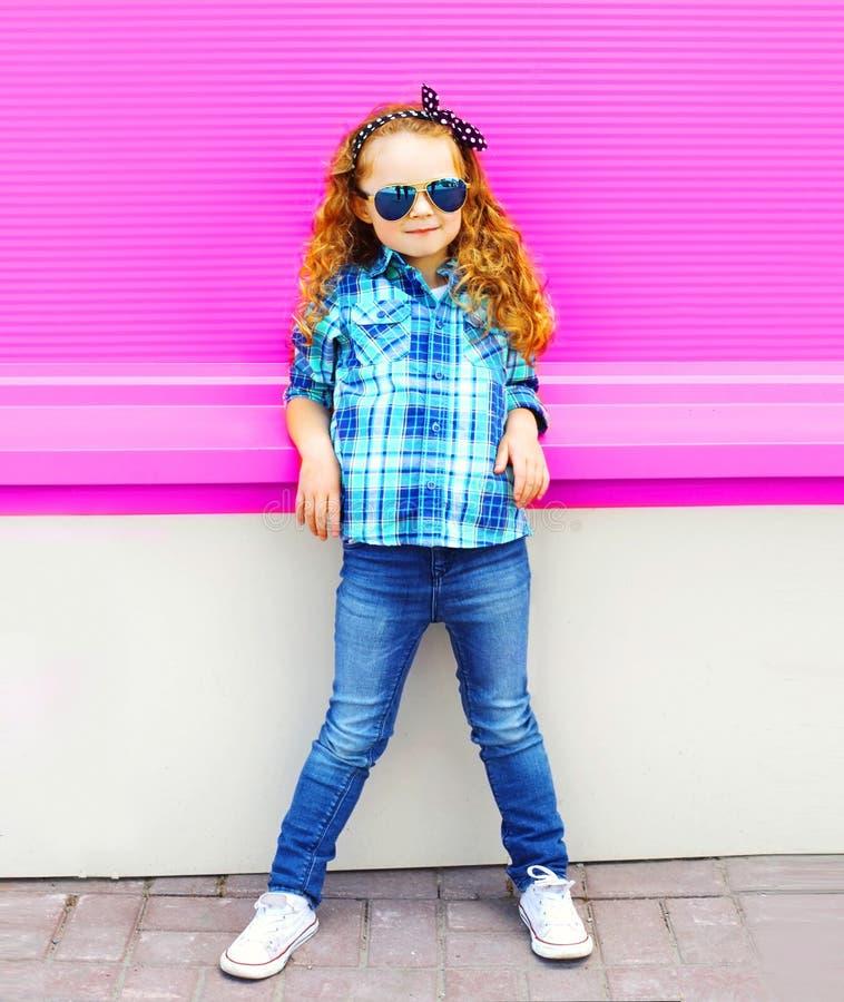 Enfant de petite fille de mode dans la chemise à carreaux, lunettes de soleil posant sur le mur rose coloré images stock