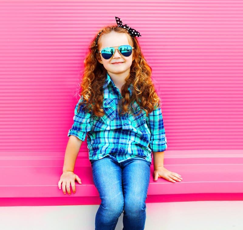 Enfant de petite fille de portrait dans la chemise à carreaux, lunettes de soleil sur le mur rose coloré photo libre de droits
