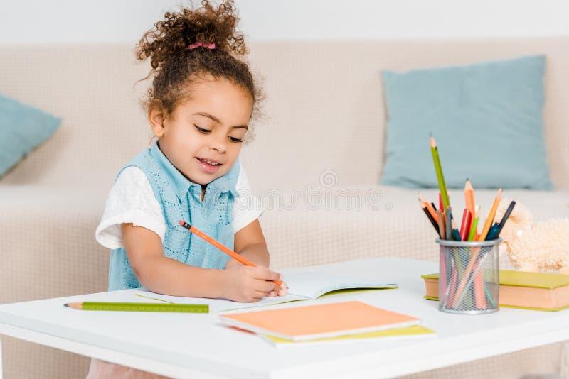 enfant de sourire adorable d'afro-américain étudiant et écrivant photographie stock