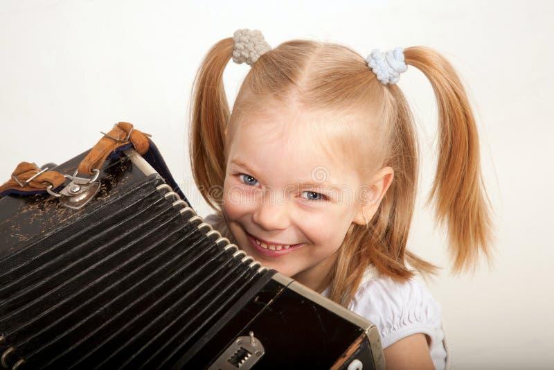 Enfant de sourire avec l'accordéon. Petit musicien. photo stock