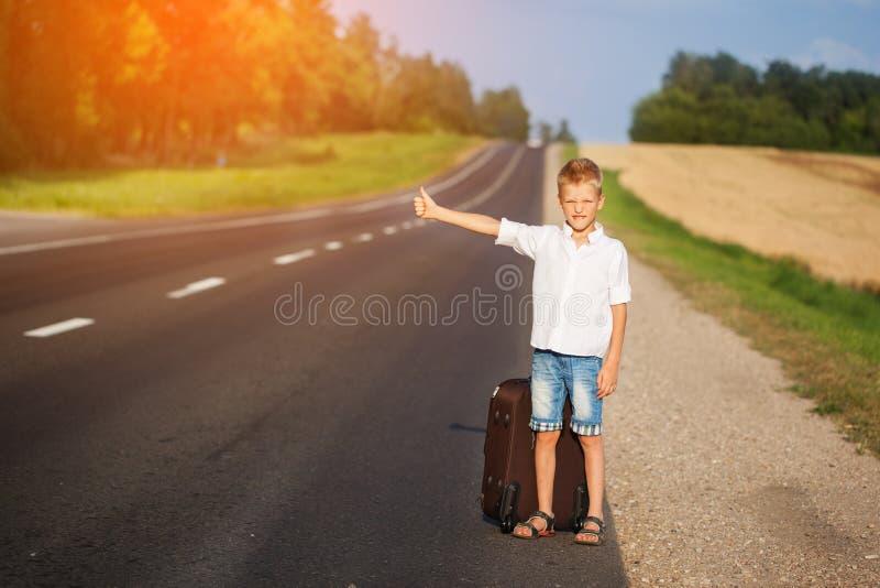 Enfant de sourire avec l'auto-stop de déplacement de valise Route d'été photographie stock libre de droits