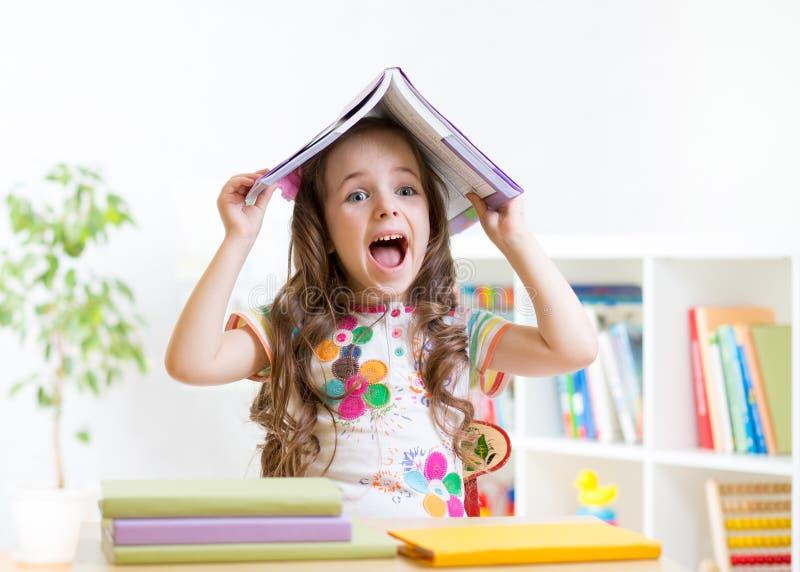Enfant de sourire avec un livre au-dessus de sa tête dans primaire image stock