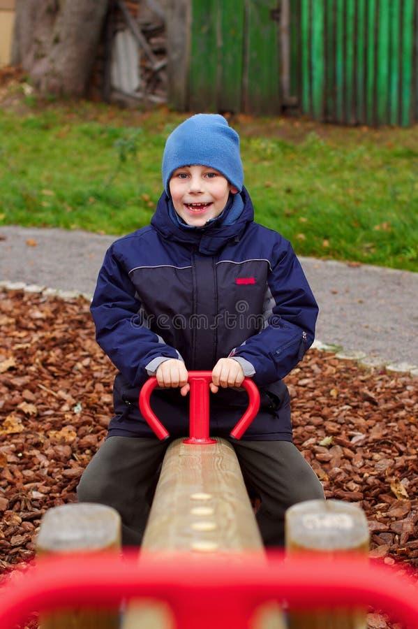 Enfant de sourire heureux dans la verticale de cour de jeu photographie stock