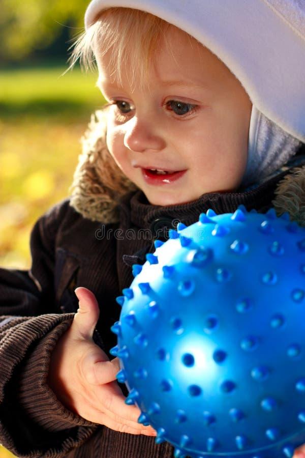 Enfant de sourire heureux de verticale avec la bille bleue image stock