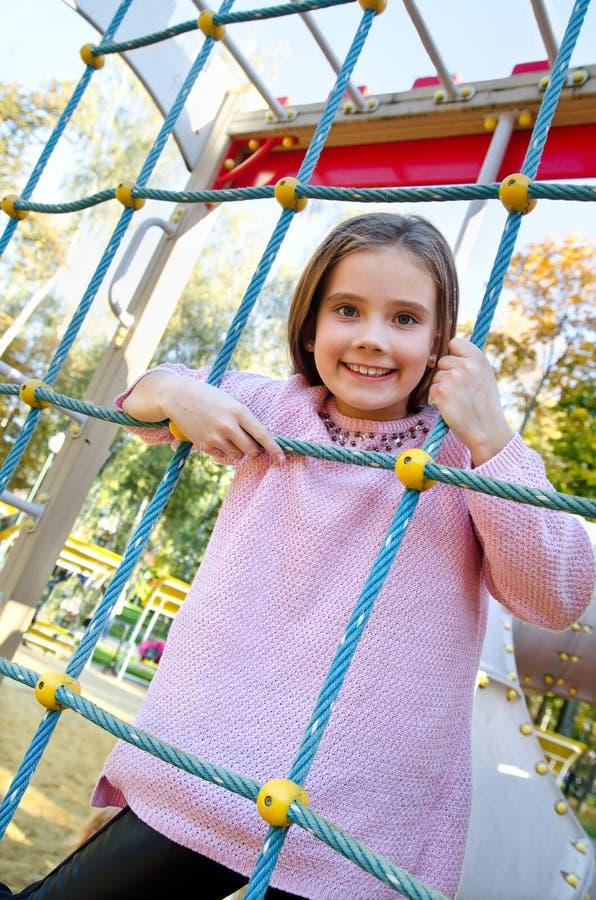 Enfant de sourire heureux de petite fille de cutu sur l'équipement de terrain de jeu photo stock