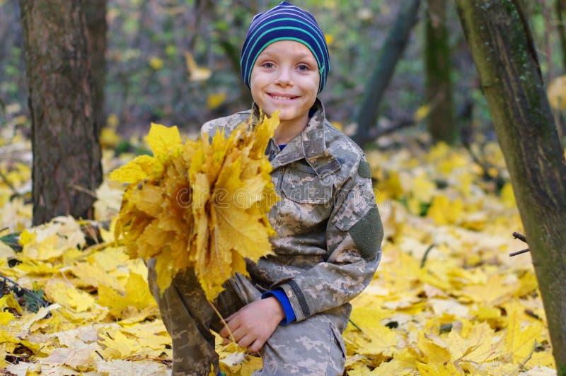 Enfant de sourire jouant avec les feuilles d'automne tombées Le garçon tenant le groupe d'érable part dans la forêt photos stock