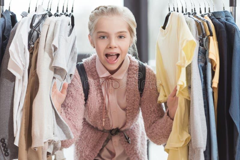 enfant de sourire regardant l'appareil-photo entouré par des vêtements sur le cintre images stock
