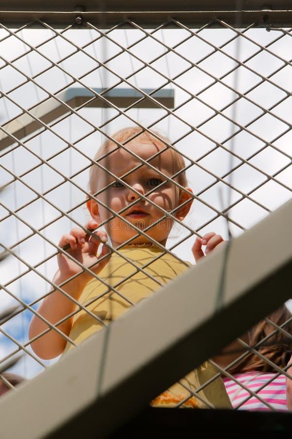 Enfant derrière une frontière de sécurité de maille photos libres de droits