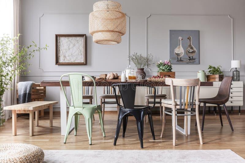 Enfant différent des chaises à la table avec les fleurs et la nourriture dans l'intérieur rustique de salle à manger avec la lamp images libres de droits