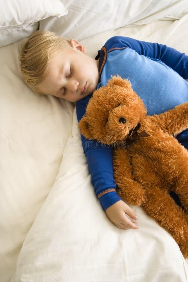Enfant dormant avec le nounours. photos stock