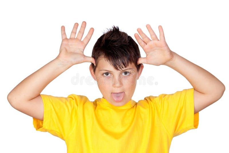 Enfant drôle avec le T-shirt jaune raillant images libres de droits