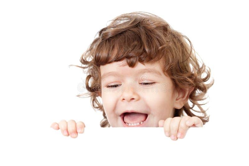 Enfant drôle bouclé retenant la publicité blanc image libre de droits
