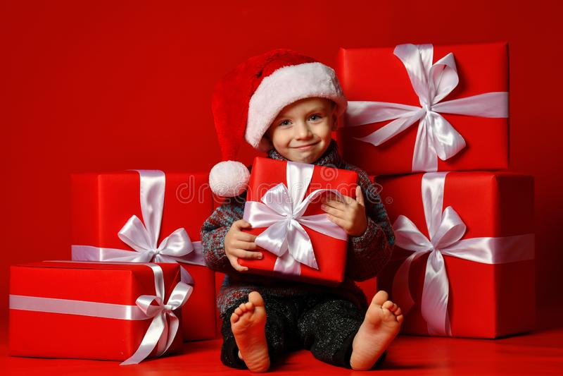 Enfant drôle de sourire dans le chapeau rouge de Santa jugeant le cadeau de Noël disponible Concept de Noël photos stock