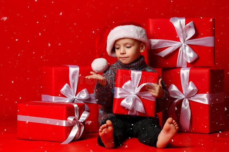 Enfant drôle de sourire dans le chapeau rouge de Santa jugeant le cadeau de Noël disponible Concept de Noël images stock
