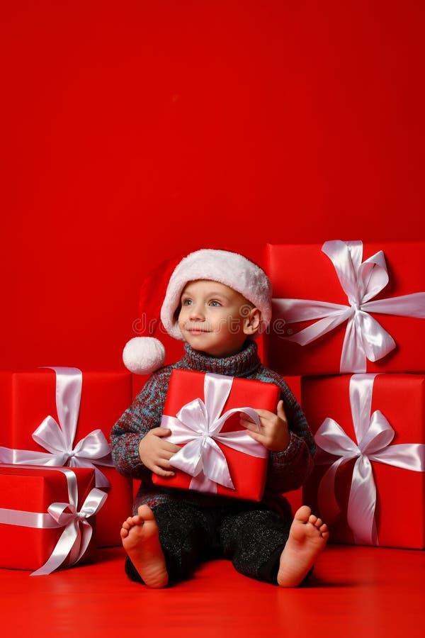 Enfant drôle de sourire dans le chapeau rouge de Santa jugeant le cadeau de Noël disponible Concept de Noël image libre de droits