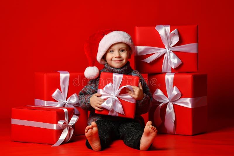 Enfant drôle de sourire dans le chapeau rouge de Santa jugeant le cadeau de Noël disponible Concept de Noël photographie stock