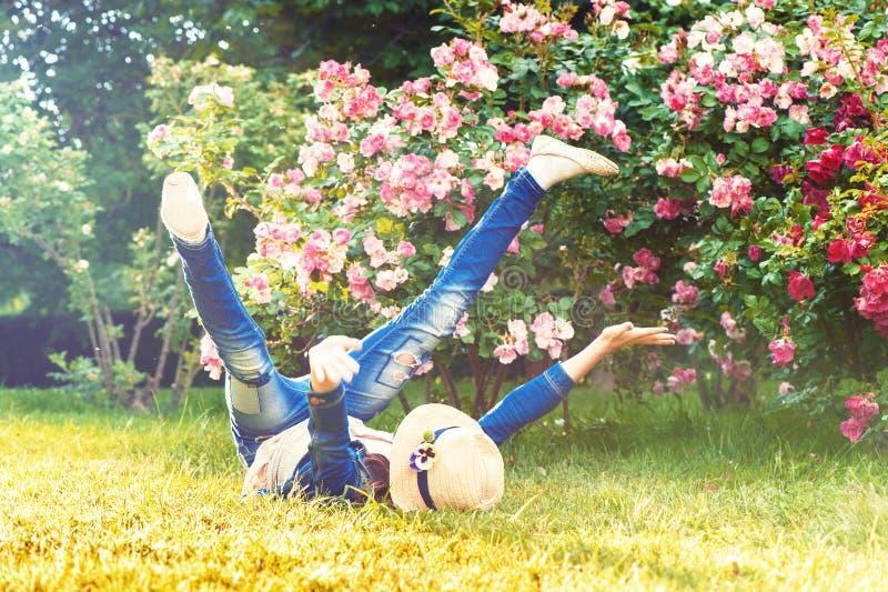 Enfant drôle heureux ayant l'amusement sur l'herbe Déranger photos stock