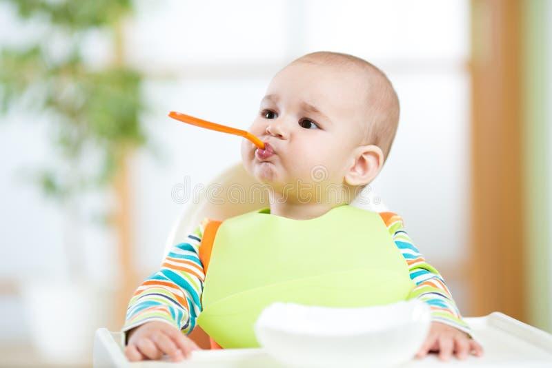 Enfant drôle avec la cuillère dans la bouche image libre de droits
