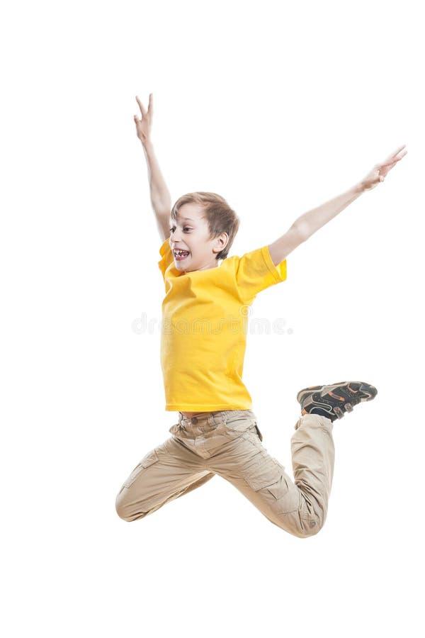 Enfant drôle dans le T-shirt coloré sautant et riant photographie stock libre de droits