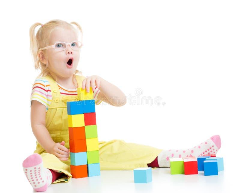 Enfant drôle dans les eyeglases faisant la tour utilisant des blocs photos libres de droits