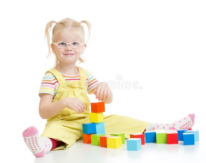 Enfant drôle dans les eyeglases jouant les blocs constitutifs photographie stock libre de droits