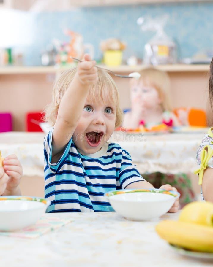 Enfant drôle jouant pendant le repas dans le jardin d'enfants images stock