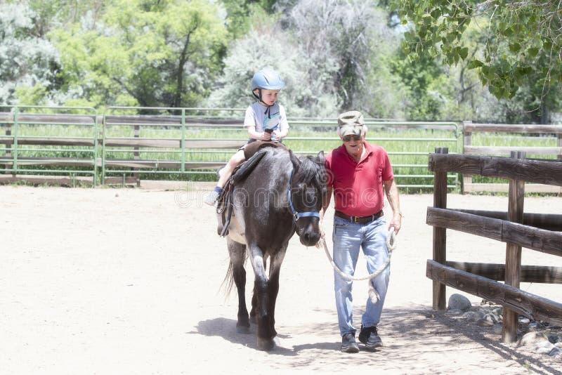 Enfant en bas âge avec un casque de sécurité sur Goes sur Pony Ride à une ferme locale avec son cheval étant première génération  photos libres de droits