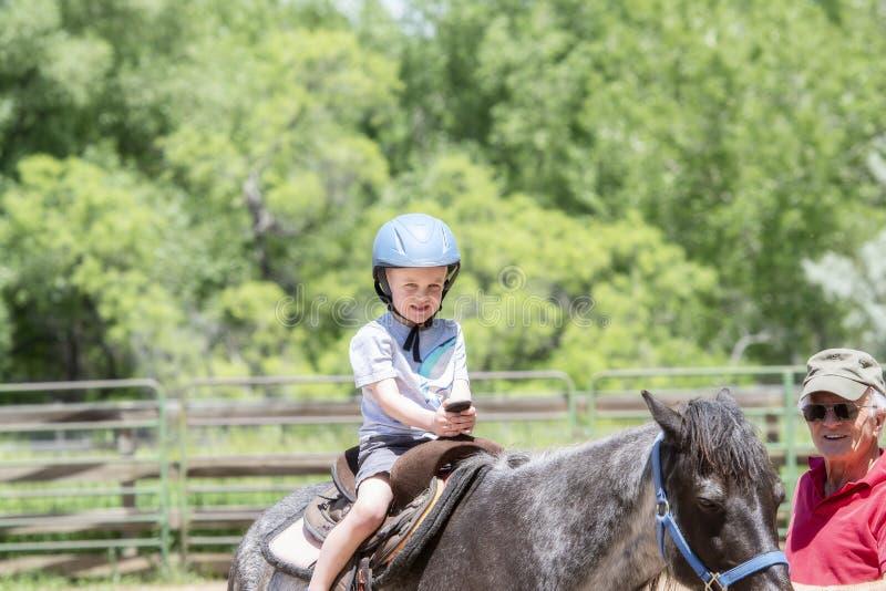 Enfant en bas âge avec un casque de sécurité sur Goes sur Pony Ride à une ferme locale avec son cheval étant première génération  images libres de droits