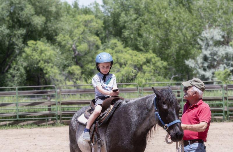 Enfant en bas âge avec un casque de sécurité sur Goes sur Pony Ride à une ferme locale avec son cheval étant première génération  photographie stock libre de droits