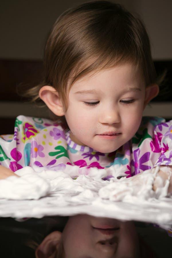 Enfant en bas âge créatif jouant avec la mousse blanche images libres de droits